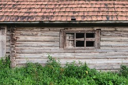 A large old wooden house in an abandoned state, the windows were broken glass, in this house lived cattle. Now there are few people in the village and everyone is old. Old window on a wooden house