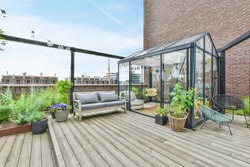 A large open-air terrace on the roof-top with lounge space and a small greenhouse with plants