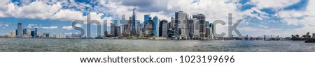 A large panoramic view spanning the New York harbor. Manhattan's Financial district is in the center, Jersey City is to the left and Brooklyn and Manhattan bridges to the right.