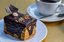 A large piece of honey cake drenched in chocolate with a cup of coffee. puff chocolate marquise.