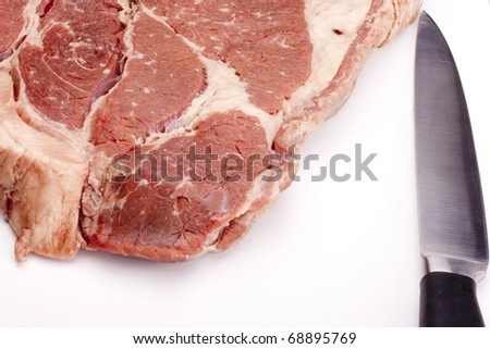 A large piece of raw meat with a kitchen knife.