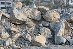 A large pile of broken rocks or mortar at large industrial construction zones.