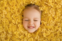 A large pile of dry noodles in the form of a bow. Pasta made from durum wheat. The child's face is surrounded by a large amount of pasta. The funny girl squeezed her eyes shut. Smile of the child