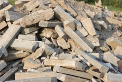 A large pile of rocks, concrete blocks and sand against the blue sky. Construction waste, concrete debris from the demolition, road.