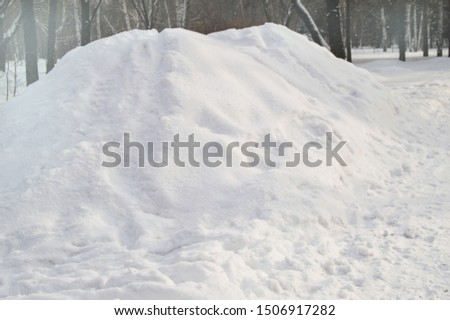 A large pile of snow piled in the Park for the construction of an ice slide, copy space, natural background