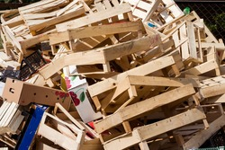 A large pile of wooden, cardboard and plastic crates on a garbage heap. Wooden and plastic and cardboard boxes from under berries on a garbage heap
