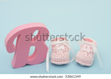 A large pink B with baby booties on a blue background, pink baby booties