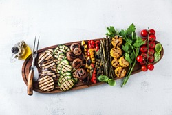 a large portion of colored grilled vegetables and mushrooms on a wooden tray on a white stone table. festive summer food