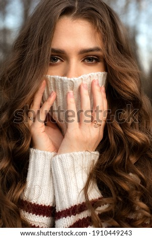 A large portrait of a girl with long chic brown curly wavy hair covers her face with a sweater, only the girl's eyes are open; a girl's look; a girl without bangs, in a sweater, without a manicure, ri Stock fotó ©