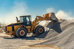A large powerful loader overloads a pile of rubble in a concrete plant.