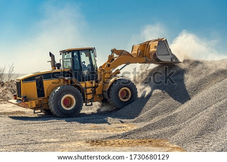 A large powerful loader overloads a pile of rubble in a concrete plant. ストックフォト ©