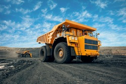 A large quarry dump truck in a coal mine. Loading coal into body work truck. Mining equipment for the transportation of minerals.