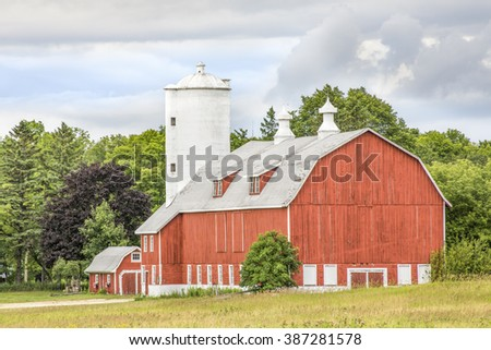 A large red barn with a tall white silo stands in scenic Door County, Wisconsin.
