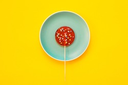 A large red Lollipop on blue plate, on a yellow background. Minimal concept.