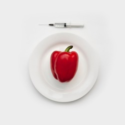 A large red pepper on a plate and a syringe with a genetically modified substance next to it. Concept image of a genetically modified product