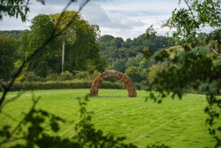 A large red stonework archway garden folly in the gardens of Rainscombe House in the village of Oare on the South facing edge of the Marlborough Downs adjacent to Pewsey Vale, Wiltshire UK