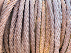 a large roll of thick corroded rusted steel metal cable wire bundle