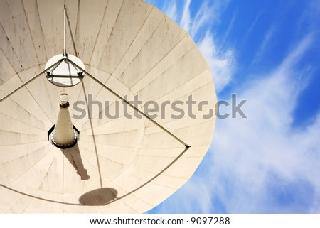 A large Satellite Dish against a blue cloudy sky. - stock photo