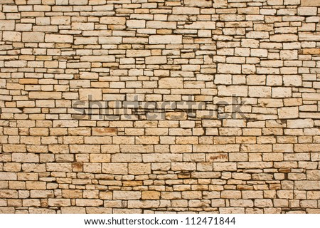 A large section of hand-cut stone wall on an historic building exterior.