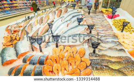 a large selection of fresh fish lying in the ice on the counter of the supermarket. Text in Russian: salmon, steak, piece, carp, Sylvia, pollock, cod, Atlantic, smelt, herring, trout, sea bass, catfis