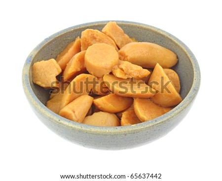 A large serving of cut canned yams in an old bowl on a white background.