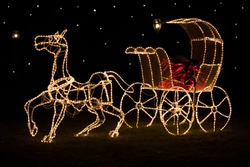 A large shining horse-drawn carriage stands in a meadow at night. Designed with golden Christmas Lights and a red shiny coachman bench.
