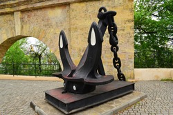 A large ship's anchor with a chain near the wall on the embankment. ship anchor, monument in Odessa. big iron black anchor. ancient maritime symbol of the city by the stone wall. nautical concept.