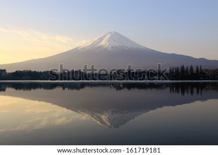 A large snow capped mountain is reflected in a calm lake.