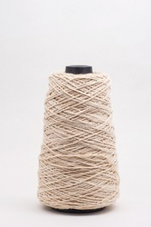 a large spool of beige cotton thread on white background