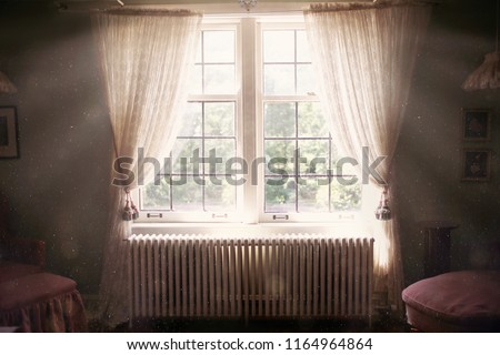 A large, sunny, and ethereal window with muntins is covered in open lace curtains, over a 1920's radiator inside a mysterious, dusty old bedroom.