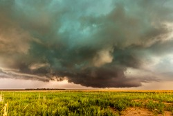 A large tornadic mesocyclone supercell inflow with a green glow of hail sucks in energy as it begins to transform into a tornado.