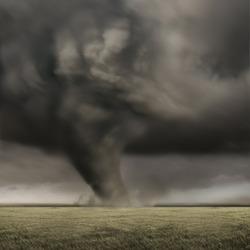 A large tornado working its way across fields.