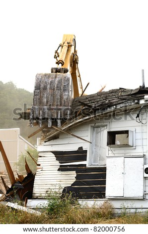 A large track hoe excavator tearing down an old hotel to make way for a new commercial development
