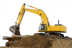 A large track hoe excavator working on removing a dirt hill for a new road project in Oregon
