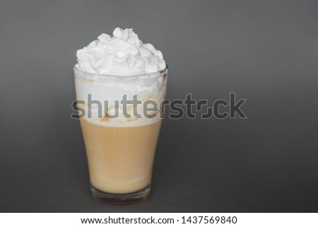 A large transparent glass filled with cold summer drink sweet coffee with whipped cream and milk is photographed on a gray, isolated background, photo for the menu #1437569840