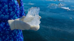 a large transparent ice floe on a man's hand