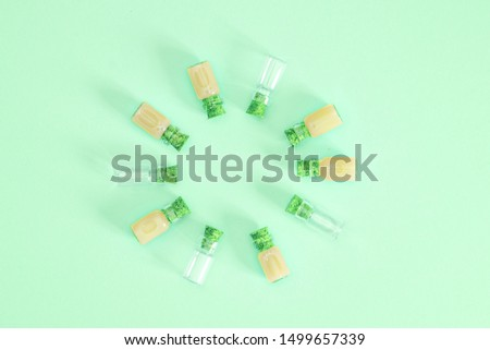 A large transparent transparent empty bottle distributes corks to the same bottles on a mint background. Top view #1499657339
