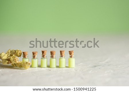 A large transparent transparent empty bottle distributes corks to the same bottles on a mint background. Top view #1500941225