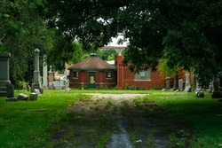 A large tree casts a dark shadow across the dirt road leading to a boarded up red brick building in a cemetery