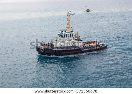 A large tugboat sailing through blue water off Aruba