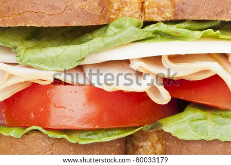 A large turkey sandwich with tomatoes, cheese, and lettuce