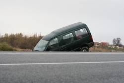 A large van is crashed in a ditch by the road.