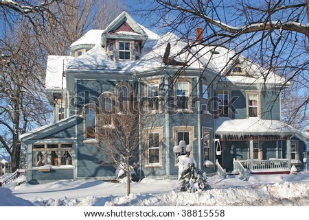 A large Victorian home covered with snow.