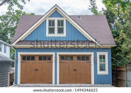 A large vintage retro detached two car cape cod blue style garage, with grey shingled roof, windows, white trim and large brown wooden garage doors, with a paved and interlocking stone driveway.