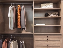 A large, walk in closet with shirts and pants hanging up on hangers and shoes on the shelving