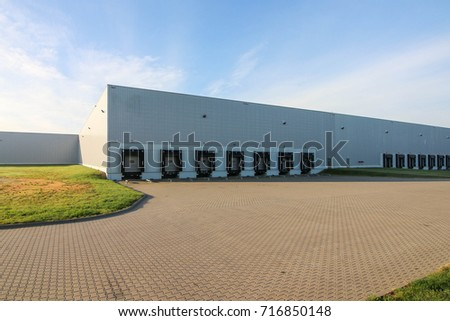 a large warehouse exterior with gates for dispatching goods #716850148