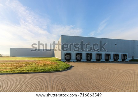 a large warehouse exterior with gates for dispatching goods  #716863549