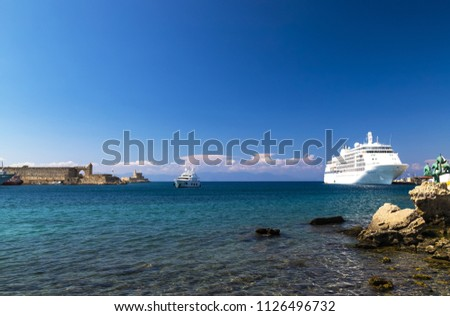 A large white cruise liner stands on a dock in a picturesque tourist sea port on the Greek island of Rhodes at sunset - the best plase for excursions, travel, recreation and vacation. Sea background\n\n