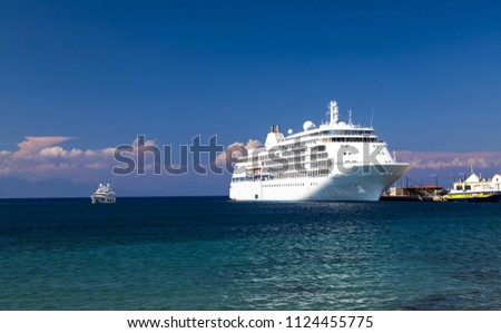 A large white cruise ship stands at the pier in the tourist sea  port at sunset, Rhodes, Greece -the best Island for excursions, travel, recreation and vacation.  Liner on sea or ocean background