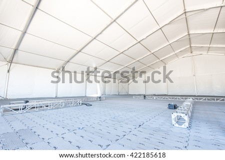 A large white tent in a grass field for parties and entertaining #422185618